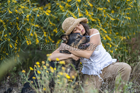 young woman wearing hat while embracing