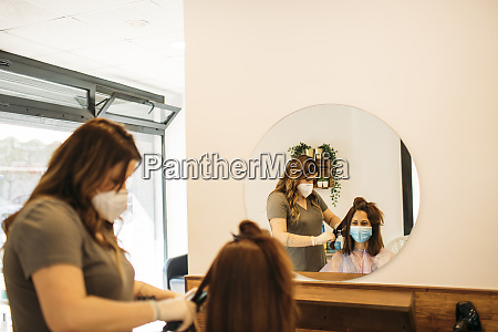 female hairdresser with mask using straightening