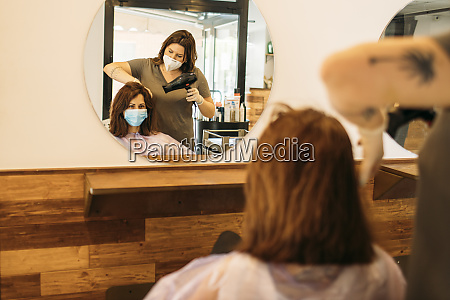 female hairdresser drying hair of female