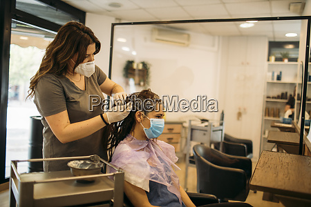 female hairdresser with mask staining hair