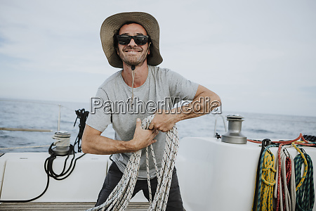 smiling sailor wearing sunglasses and hat