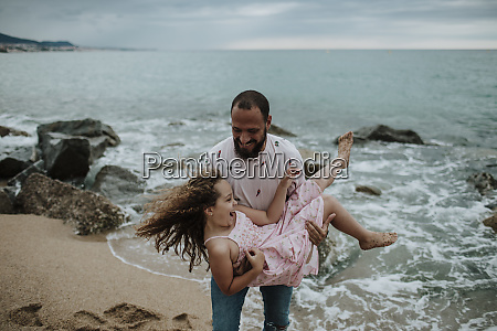 smiling father carrying daughter at beach
