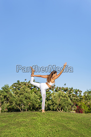 woman doing yoga on lawn in