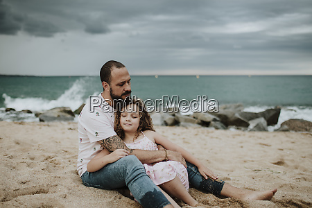 father embracing daughter while sitting on