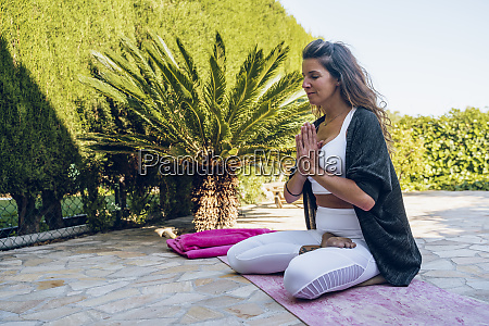 woman sitting on terrace in yoga
