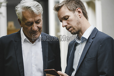 two businessman standing in backyard using