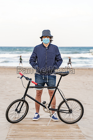 mature man with bicycle standing on