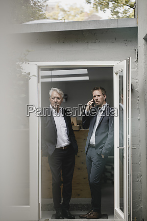 two businessmen staning in open office