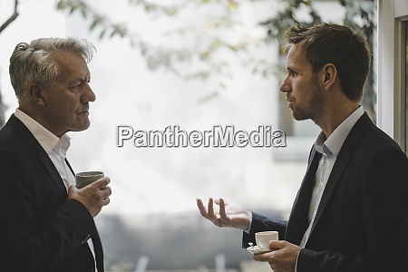 two businessmen discussing in office
