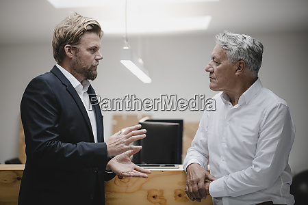 business partners standing in office talking