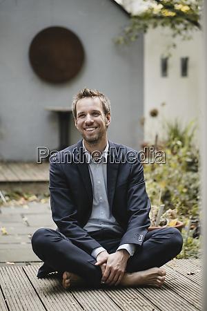 laughing businessman sitting cross legged in