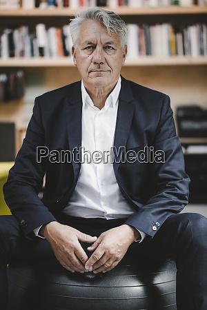 senior businessman sitting on fitness ball