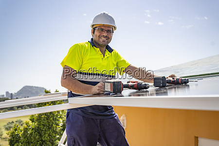 portrait of smiling mature technician installing