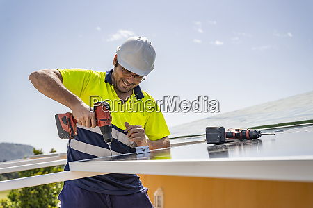 smiling mature technician installing solar panel