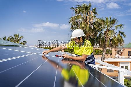 mature technician installing solar panel on