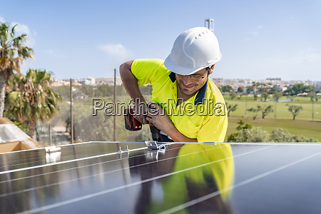 male technician installing solar panel with