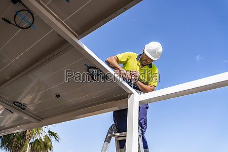 mature technician installing solar panel on