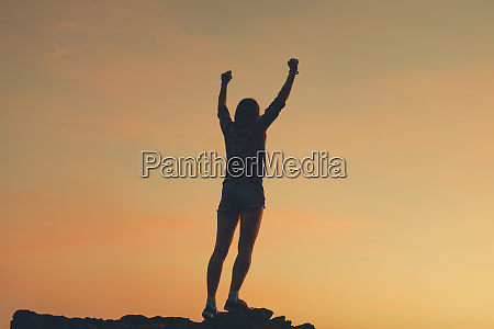 silhouette of woman with raised arms
