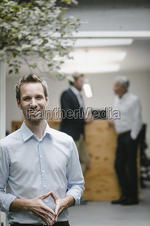 businessman standing in open office door