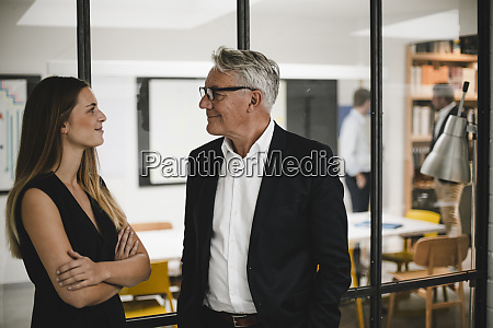 young woman talking to senior businessman