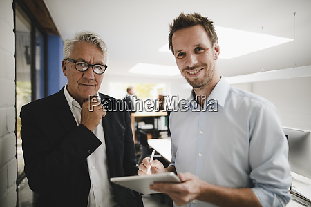 two successful businessmen standing in office