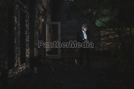 senior businessman standing in backyard at