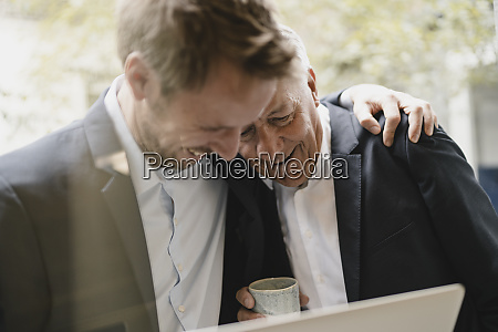 father leaning on shoulder of his