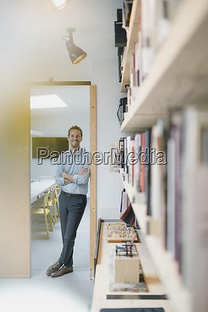 businessman leaning in door of his
