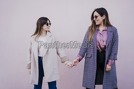two fashionable friends holding hands