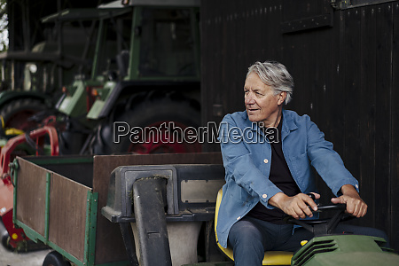 senior man driving tractor with trailer