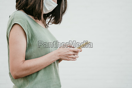 woman wearing protective mask using cell