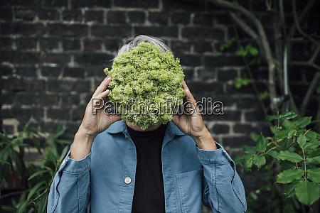 senior man holding a lettuce head