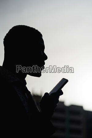 silhouette of businessman with mobile phone