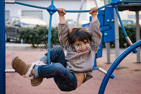 girl on climbing net in playground