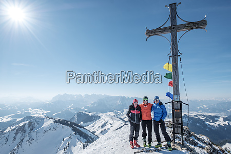 friends standing by cross on snowcapped