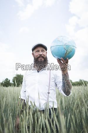 bearded man holding globe looking away