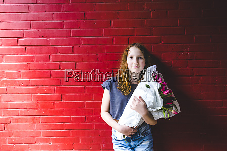 girl holding bouquet while standing against
