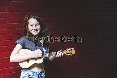 smiling girl playing ukulele while standing