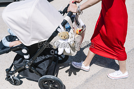 mother pushing son in baby carriage