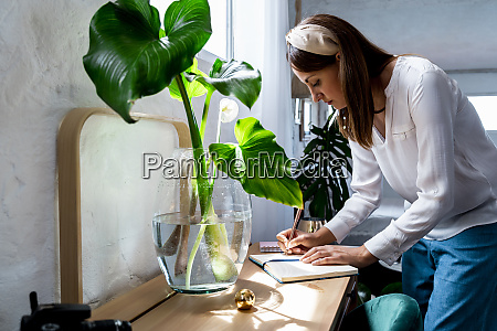 woman writing in diary at desk