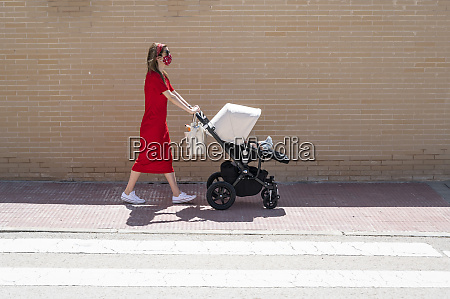 mother wearing mask pushing son in
