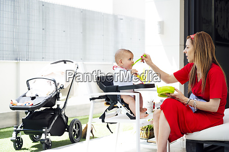 mother feeding cute son while sitting