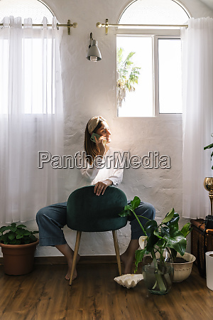 woman using mobile phone while sitting