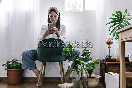 smiling woman using smart phone while