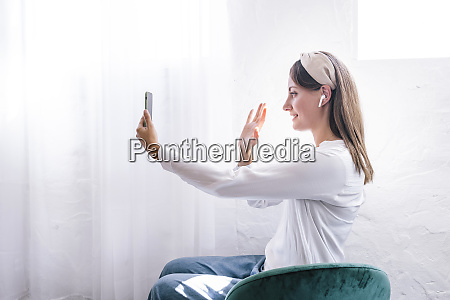 smiling woman waving while enjoying video