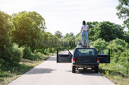 woman standing by dog on vehicle
