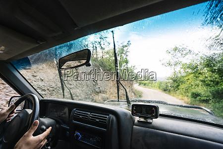 hands of man on steering wheel