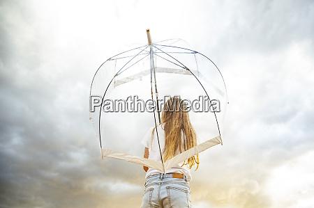 blond girl holding transparent umbrella during