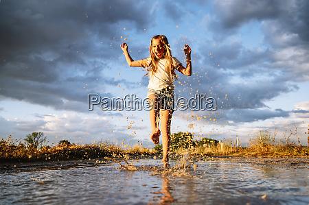 cheerful girl splashing water on puddle