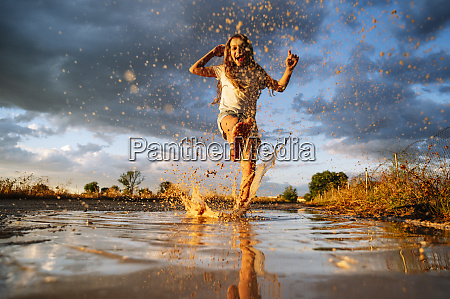 happy girl playing while splashing water